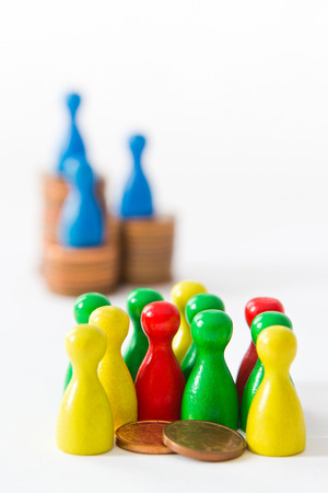group of game figurines huddling around two cents while very few are on top of stacks, concept  unequal distribution of wealth Stock Photo - 23981744