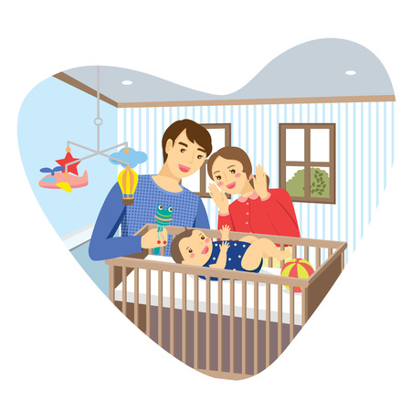 Family with baby in bedroom with heart shape frame. Mommy playing peekaboo with baby boy lying in a cot. Daddy holding baby rattle.