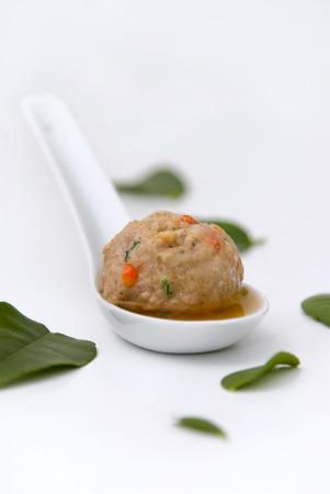 kafir lime: A pork meatball, with chili, in a kafir lime leaf broth served on a small white spoon. Stock Photo