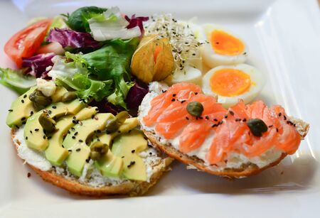 food, fried eggs with toast and mousse and salmon and avocados on a plate