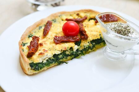 quiche with spinach with herbs and sluggish tomatoes and cherry, creamy sausage on a white plate