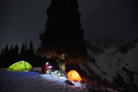Man sits near a tents at night in the winter in the mountains 版權商用圖片