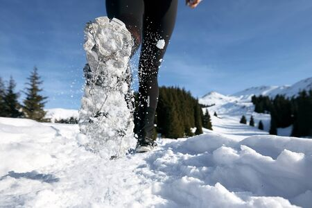 Close-up shoes of trail runner woman running in winter mountains trail on snow.