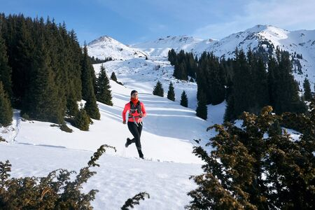 Trail runner woman running in winter mountains trail on snow.