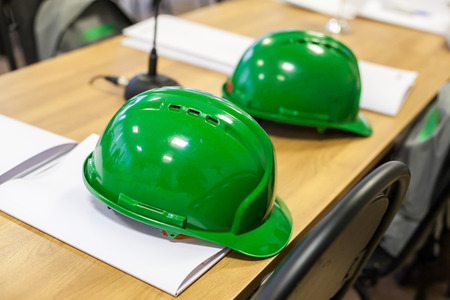 architect tools: Green hard hats on the wooden table. Green Safeti helmets Stock Photo