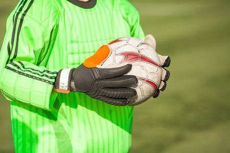 junior soccer: Junior league on soccer. Close up of the hands of the goalkeeper holding a soccerball.