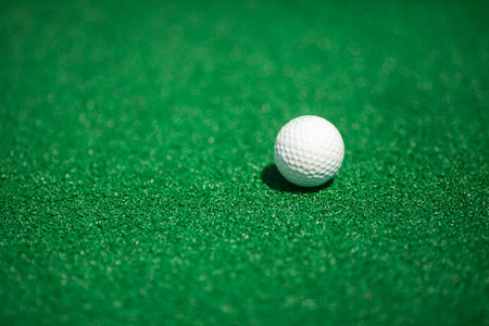 Ball for golf on a green field. A white ball for golf. Stock Photo