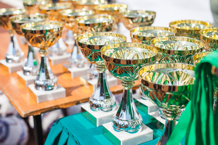 the victorious: Victorious cups in sports meets. Cups of winners. Trophy cups. Trophy cups on the table.