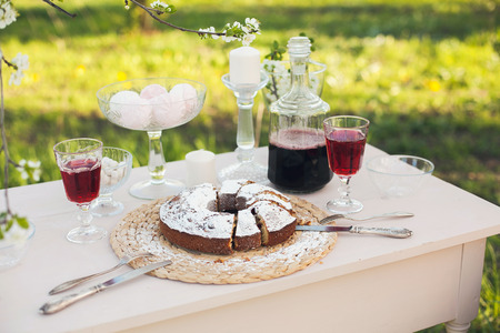strewed: The cake strewed with icing sugar on a table. Freshly baked sweet cake. Festive breakfast. Breakfast outdoors. Festive lunch outdoors. Festive dinner outdoors. Table layout outdoors. Baking on a table. Summer dinner outdoors. Stock Photo