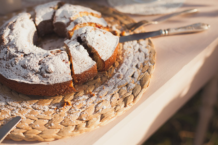 strewed: The cake strewed with icing sugar on a table. Freshly baked sweet cake. Festive breakfast. Breakfast outdoors. Festive lunch outdoors. Festive dinner outdoors.Freshly baked sweet cake closeup . Baking on a table. Summer dinner outdoors.