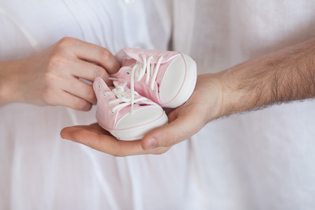 The husband touches a stomach of the pregnant wife. The man and the woman waiting for the child. Waiting for the baby. The loving parents. Hands of the woman holding small shoes for a baby.
