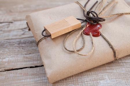 Il pacco avvolto in Kraft su uno sfondo di legno. Il regalo avvolto in Kraft. chiavetta USB in legno. Cord e ceralacca rossa.
