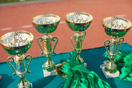 Victorious cups in sports meets. Cups of winners. Trophy cups close up. Stock Photo