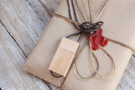 sealing: The parcel wrapped in Kraft on a wooden background. The gift wrapped in Kraft. Wooden USB stick. Cord and red sealing wax.