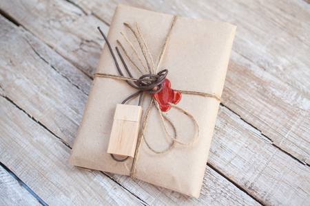 The parcel wrapped in Kraft on a wooden background. The gift wrapped in Kraft. Cord and red sealing wax.