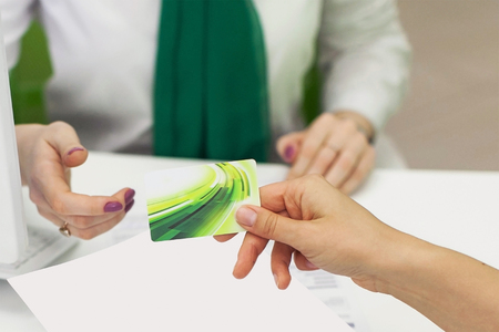 accepts: Female hand with a blank card. The bank worker accepts the credit card.