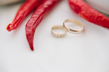 gold wedding rings and red hot peppers on a white background.