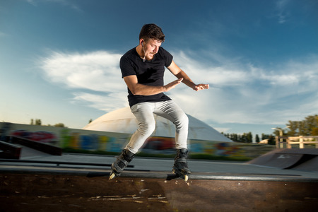blader: the handsome man with a beard in casual clothes shows driving elements on rollers on a stage. aggressive inline skating. Roller blader does a trick. Perfect balance and high speed.