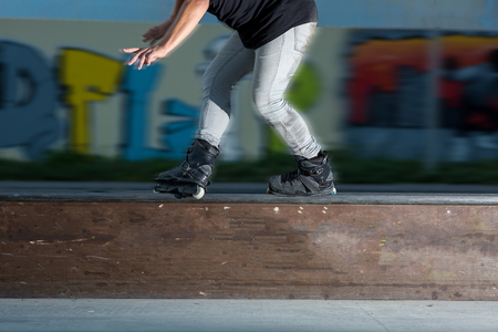 blader: Young man rollerblading. Roller blader near graffiti. Not afraid of speed. Legs of person on inline skates close up. driving concept on rollers on a stage.