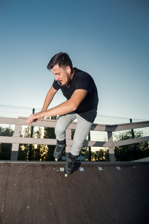 blader: Stylish guy roller blading and listening to music in earphones outdoors. Roller blader on ramp. High speed and dangerous tricks. Stock Photo