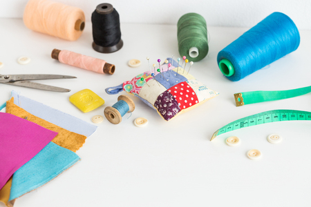 kit de costura: Sewing tools including fabric, scissors, needles, pins, spools of different color thread, measure tape, buttons on a white background with a empty space for the text. Sewing tools fashion design.