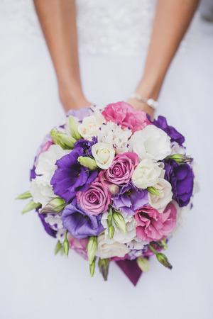 Bride in a white wedding dress holding a flowers bouquet from bride in a white wedding dress holding a flowers bouquet from purple rose in hands mightylinksfo