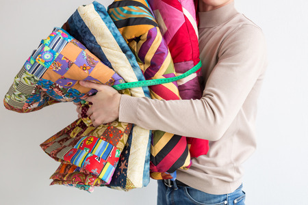 quilting and patchwork at workshop of tailor male - tailor holds in his hands near chest stitched multi-colored patchwork fabric, which are connected by the measuring tape. Sewing concept. Banco de Imagens