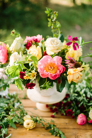 bouquet, holiday flower, gifts and floral arrangement concept - white vase with a beautiful bouquet on a wooden table, decorative arrangement of yellow and white roses, pink peons, daisies, carnations