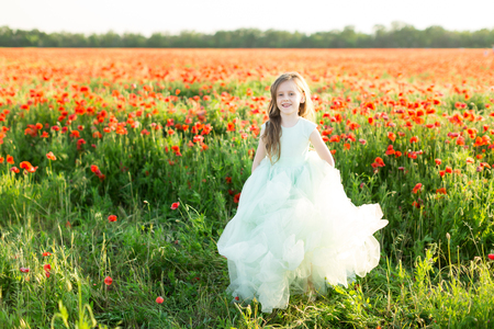 girl model, poppies, childhood, fashion, children, nature and summer concept - on the sunny field of poppies is a beautiful smiling little girl - princess, she is dressed in a festive blue dress Stock Photo