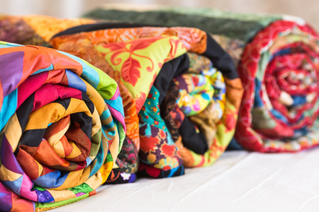 Three colored patchwork quilts twisted into close up. Colorful scrappy blankets folded as background. Handmade, hobby, art concept. Фото со стока