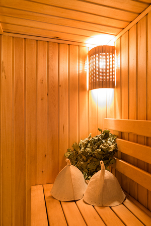 finnish bath: Interior of a sauna . Advantage for health. Oak brooms for a steam room in traditional russian wooden bath. Leaf Venik With Dried Herbs in wooden sauna bucket and sauna hat.