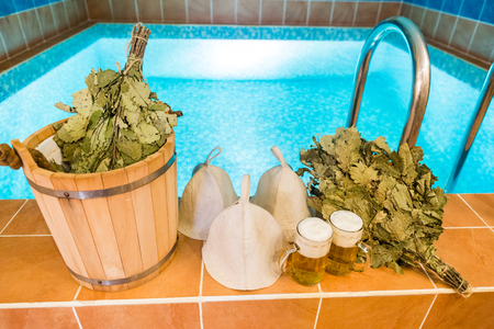 Bath accessories in the Russian bath. Bathroom items of traditional Russian sauna. two mugs of light beer, bathing caps, bath brooms from oak leaves. Recreation, spa, relaxation, rest concept.