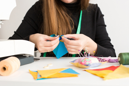 needlework and quilting in the workshop of a young woman - close up on hands of a tailor sews with a needle pieces, colorful fabrics on the desktop with threads, scraps of fabric and spin cushion Stock Photo