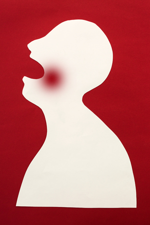concept of human disease diagnosis and pain localization on silhouette - contour of abstract white male man with opened mouth and dental sore, isolated on red background, top view, flat lay Stock Photo