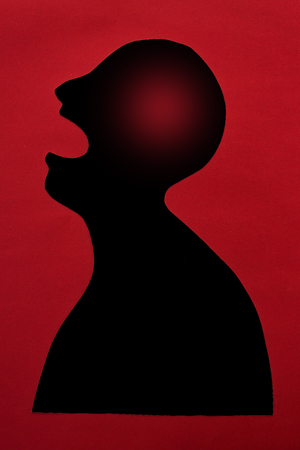 concept of human disease diagnosis and pain localization on silhouette - contour of abstract black male man with significant brain damage, opened mouth, isolated on red background, top view, flat lay