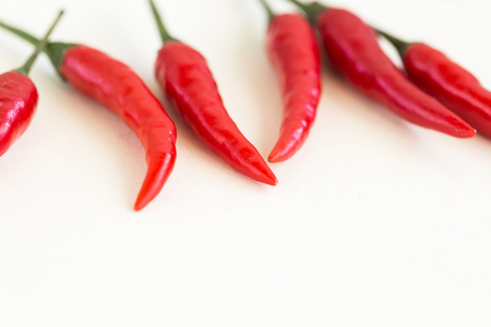 freely: red hot chili peppers, popular spices concept - macro of few fresh pods of red chili peppers isolated on white background, collage of freely lying peppers, selective focus, free space for text Stock Photo