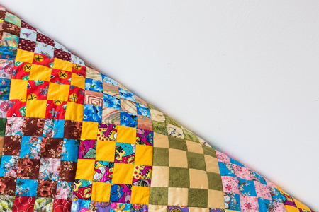 homemade, patchwork, quilting, sewing, comfort concept - multicolored handmaded blanket in best russian traditions made of textile squares with floral and abstract prints. with empty space for text Stock Photo