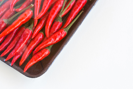 red hot chili peppers, popular spices concept - store packing of weighted red spicy peppers, peppers packing under plastic film in a dark disposable tray on white background - space for text Stock Photo