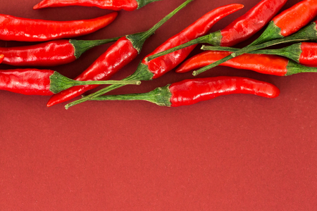 red hot chili peppers, popular spices concept - close-up on a beautiful handful of red hot pepper pods scattered on red background, top view, flat lay, free space for your text Stock Photo