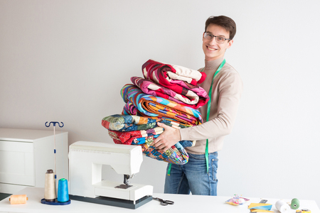 patchwork and quilting - smiling tailor male carries a stack of stitched colored fabric, he is near the table with a sewing machine, the neck hanging measuring tape Stock Photo