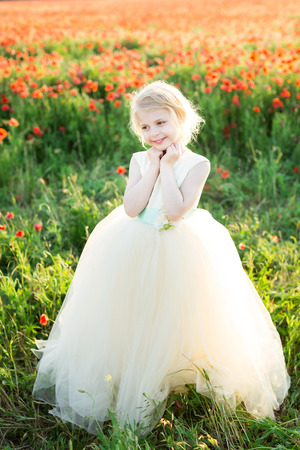 girl model, poppies, wedding, fashion children, nature and summer concept - elegant sweetheart girl bridesmaid with white hair flirts, plays in a field of poppies, she in a white wedding dress Stock Photo