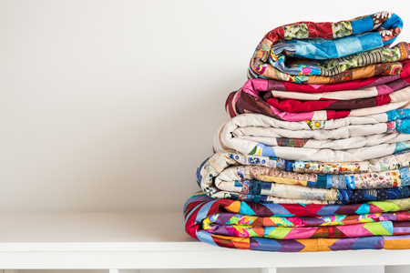 sewing and fashion concept - stack of colorful quilts, beautiful bedspreads stacked in several rows in height for storage, sale patchwork productions on a white background, copy space