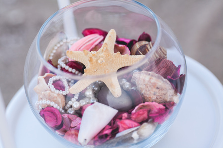 easily soiled stars, cockleshells, pearls lying in transparent to a glass vase with violet and pink petals. Summer mood, love, romantic, sea , ocean concept. sea wedding decor.