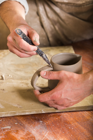 fireclay: pottery, stoneware, ceramics art concept - closeup of craftsman hands connect handle to cup with tool, master fingers work with pieces of fireclay, male stand at workshop behind table, vertical Stock Photo