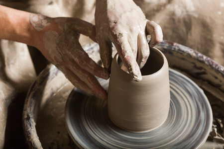 fireclay: pottery, workshop, ceramics art concept - closeup on male hands sculpt some new utensil with fingers and water, man hands works with potters wheel and raw fireclay, top view Stock Photo