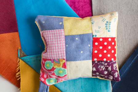 patchwork, quilting, sewing, tailoring and fashion concept - macro on pillow with background of blue, gray and sand flaps of fabric, closeup on beautiful colorful stitched cushion, flat lay, top view