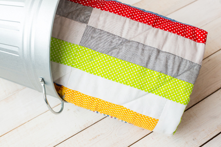 counterpane: patchwork and fashion concept - close-up on beautiful quilt in a metal bucket on a whitewashed wooden floor, close-up on patchwork products on a light background, top view