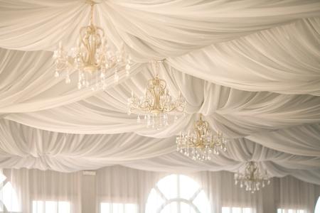 웨딩 파티에서 천막 천막에 황금 샹들리에. 흰색 텐트에서 결혼식 장식입니다.