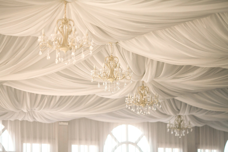 gold chandeliers on an tents ceiling in a wedding party. wedding decor in a white tent. Stock Photo