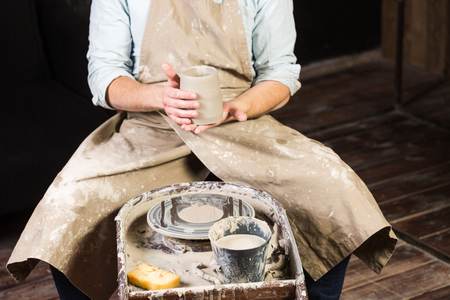 fireclay: pottery, workshop, ceramics art concept - closeup on male hands holding unfired clay cup, a man examines a fresh product before further processing, master sits at the Potters wheel, front view